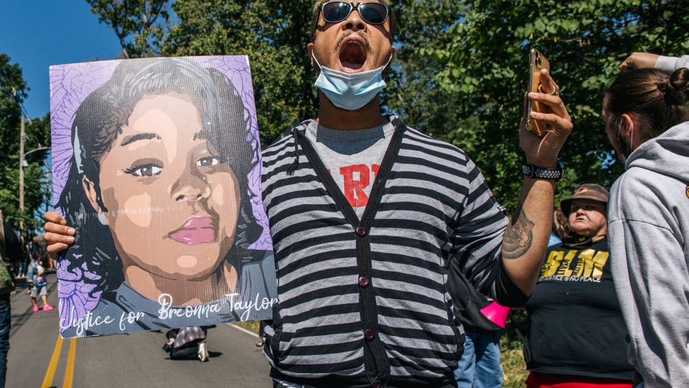 A demonstrator holds up a sign of Breonna Taylor while chanting during a protest in wake of Supreme Court Justice Ruth Bader Ginsburgs death in front of Senate Majority Leader Sen. Mitch McConnells home on September 19, 2020 in Louisville, Kentucky.