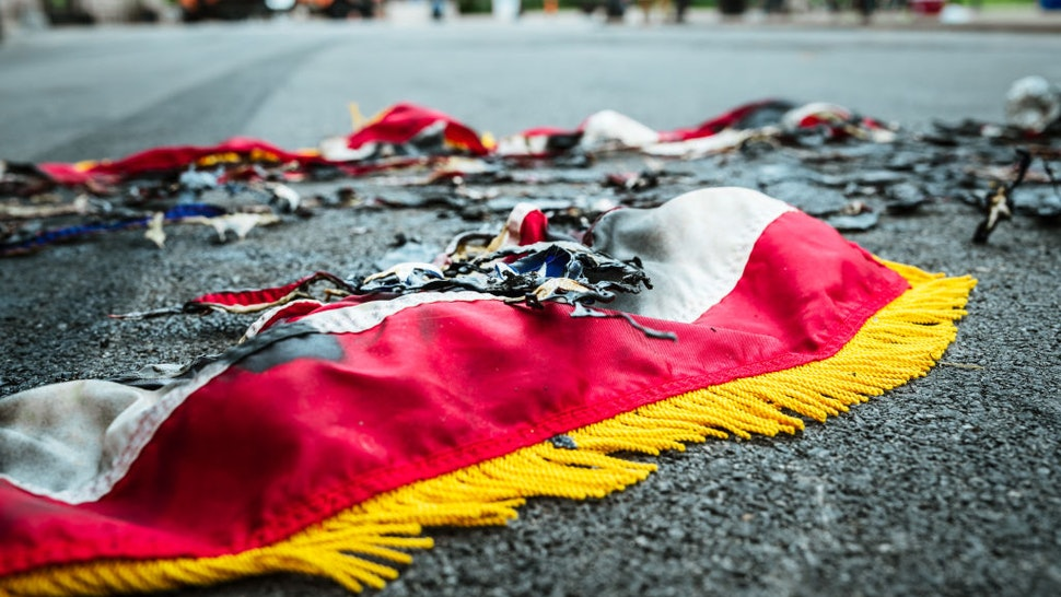 LOUISVILLE, KY - SEPTEMBER 22: The remnants of an American flag sit charred on the road near Jefferson Square Park on September 22, 2020 in Louisville, Kentucky. Jefferson Square Park has remained the epicenter for Louisville protest action following the March 13th killing of Breonna Taylor by police during a no-knock warrant at her apartment. (Photo by Jon Cherry/Getty Images)