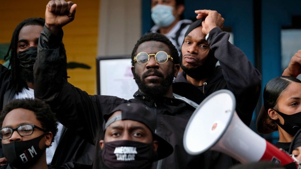 Demonstrators stand on the steps of a local business in the NULU neighborhood on a third day of protest over the lack of criminal charges in the police killing of Breonna Taylor and the result of a grand jury inquiry, in Louisville, Kentucky, on September 25, 2020