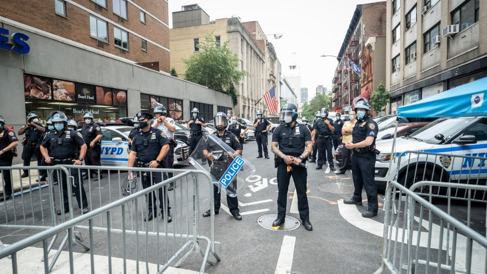 A line of police in protective helmets and riot shields wait to meet Derrick Ingram and supporters on August 08, 2020 in the Manhattan borough of New York City.