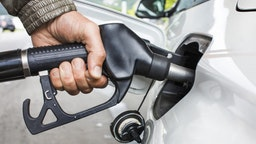 Mans's hand holding fuel nozzle in car - stock photo