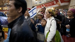 Jewish immigrants of the Bnei Menashe tribe reunite with relatives at the Ben Gurion airport on December 24, 2012 near Tel Aviv, Israel.