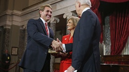 U.S. Sen. Jeff Flake (R-AZ) (L) participates in a reenacted swearing-in with his wife Cheryl Flake (C) and U.S. Vice President Joe Biden in the Old Senate Chamber at the U.S. Capitol January 3, 2013 in Washington, DC.