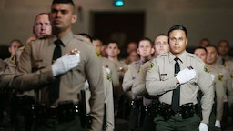 MONTEREY PARK, CALIFORNIA - AUGUST 21: Graduates of Los Angeles County Sheriff's Department Academy Class 451 stand for the pledge of allegiance at their graduation ceremony at East Los Angeles College amid the COVID-19 pandemic on August 21, 2020 in Monterey Park, California. Graduates were seated with social distancing and family members were not allowed inside the ceremony due to restrictions in place to prevent the spread of the coronavirus. (Photo by Mario Tama/Getty Images)