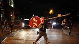 A demonstrator carries a traffic stop sign while marching during a protest in Louisville, Kentucky, U.S., on Thursday, Sept. 24, 2020. Wednesday's decision not to charge Kentucky police officers for the killing of Breonna Taylor ignited a fresh wave of protests in the U.S. Photographer: Luke Sharrett/Bloomberg via Getty Images