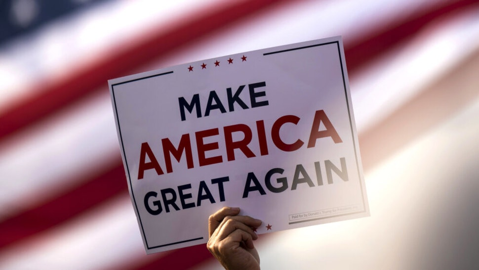 "BEMIDJI, MN - SEPTEMBER 18: A man waves a ""Make America Great Again"" sign before President Donald Trump arrives for a rally at the Bemidji Regional Airport on September 18, 2020 in Bemidji, Minnesota. Trump and challenger, Democratic presidential nominee and former Vice President Joe Biden, are both campaigning in Minnesota today."