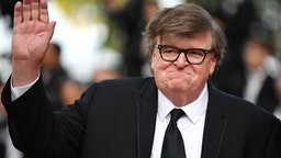 """US director Michael Moore waves as he arrives for the screening of the film """"The Specials (Hors Normes)"""" at the 72nd edition of the Cannes Film Festival in Cannes, southern France, on May 25, 2019."""