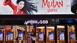 """People buy tickets for Disneys Mulan film at a cinema inside a shopping mall in Bangkok on September 8, 2020. - Disney's """"Mulan"""" remake is facing fresh boycott calls after it emerged some of the blockbuster was filmed in China's Xinjiang, where widespread rights abuses against the region's Muslim population have been widely documented."""