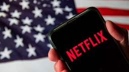 CHINA - 2020/08/13: In this photo illustration the American global on-demand Internet streaming media provider Netflix logo is seen on an Android mobile device with United States of America flag in the background.