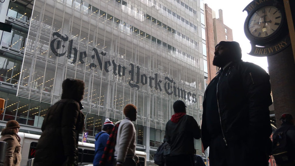 People walk past the front of the New York Times building on November 21, 2018 in New York City. (Photo by Gary Hershorn/Getty Images)