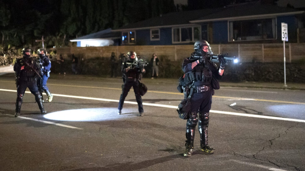 PORTLAND, OR - AUGUST 30: A Portland police officer points a less lethal weapon at anti-police protesters near the east police precinct a day after political violence left one person dead on August 30, 2020 in Portland, Oregon. City leaders asked for calm and time to conduct an investigation after a man was shot and killed near a pro-Trump rally on Saturday.