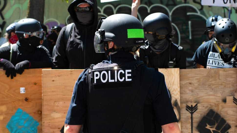 SEATTLE, WASHINGTON - AUGUST 9: A police officer stands in front of counter protesters during the Seattle Police Officers Guildâs rally to stop defunding of the Seattle Police Department on Sunday, August 9, 2020 at Seattle City Hall. The Seattle City Council passed a resolution to reduce the Seattle Police Department by up to 100 officers through layoffs but the council failed to pass a 50% cut of the Police Departmentâs remaining 2020 budget on August 5, 2020.