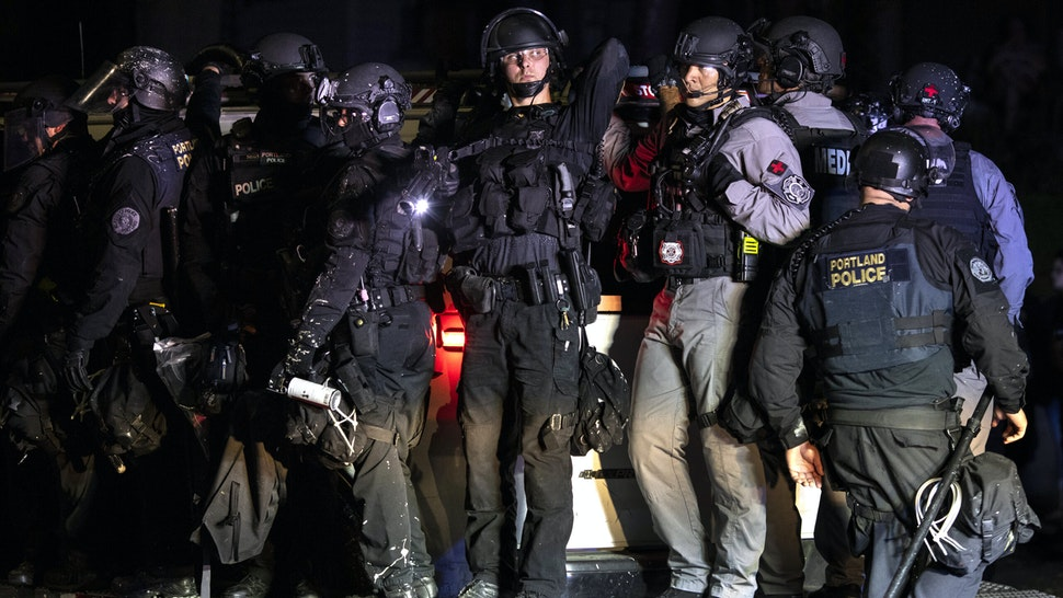 Portland police are seen in riot gear during a standoff with protesters in Portland, Oregon on August 16, 2020. Protests have continued for the 80th consecutive night in Portland since the killing of George Floyd.