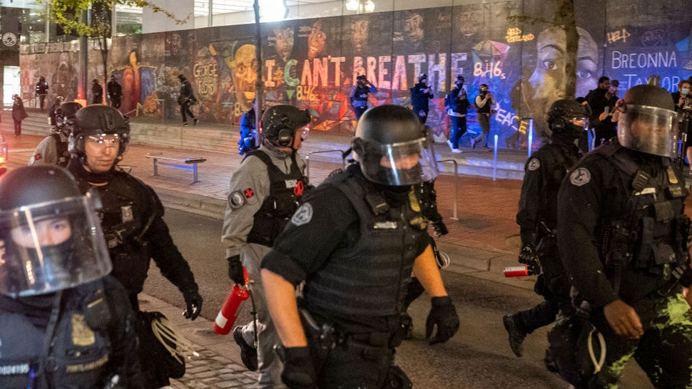 Portland police disperse a crowd of protesters past a mural of George Floyd and Breonna Taylor on September 26, 2020 in Portland, Oregon. Oregon Governor Kate Brown declared a state of emergency prior to Saturday's protest and Proud Boy rally, as fears of political violence between far-right groups and Black Lives Matter protesters grew. (Photo by Nathan Howard/Getty Images)