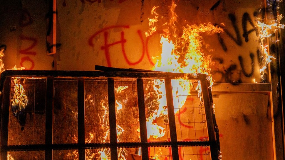 PORTLAND, OREGON, USA - AUGUST 28: About two hundred persons protesting police brutality spray graffiti and start fires at the Portland Police Union building, in Portland, Oregon, United States on August 28, 2020, the 93rd day of consecutive protests. Police declared a riot and arrested many people.