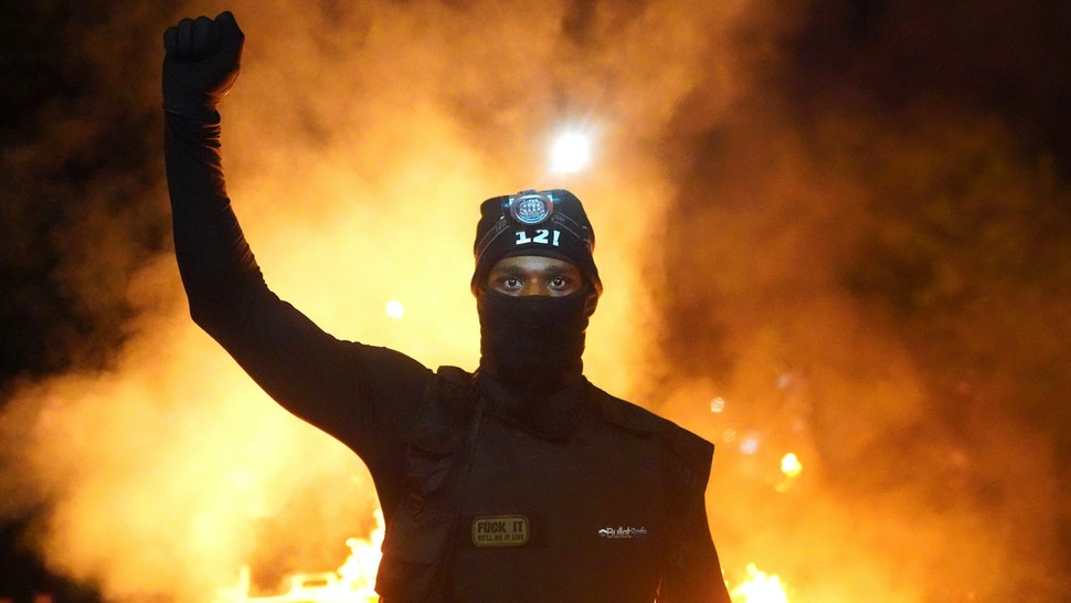PORTLAND, OR - AUGUST 23: A protester holds his fist in the air during a protest against racial injustice and police brutality early in the morning on August 23, 2020 in Portland, Oregon. Hundreds of protesters clashed with police Saturday night following a rally in east Portland.