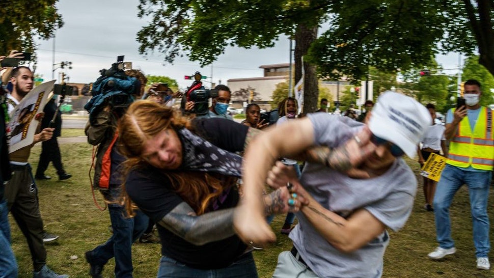 """A protester scuffles with a Trump supporter (R) in Kenosha, Wisconsin, on September 1, 2020, amid ongoing demonstrations after the shooting by police of Jacob Blake. - President Donald Trump on September 1 took his tough law and order message to Kenosha, the latest US city roiled by the police shooting of a black man, as he branded recent anti-racism protests acts of """"domestic terror"""" by violent mobs. (Photo by Kerem Yucel / AFP) (Photo by KEREM YUCEL/AFP via Getty Images)"""
