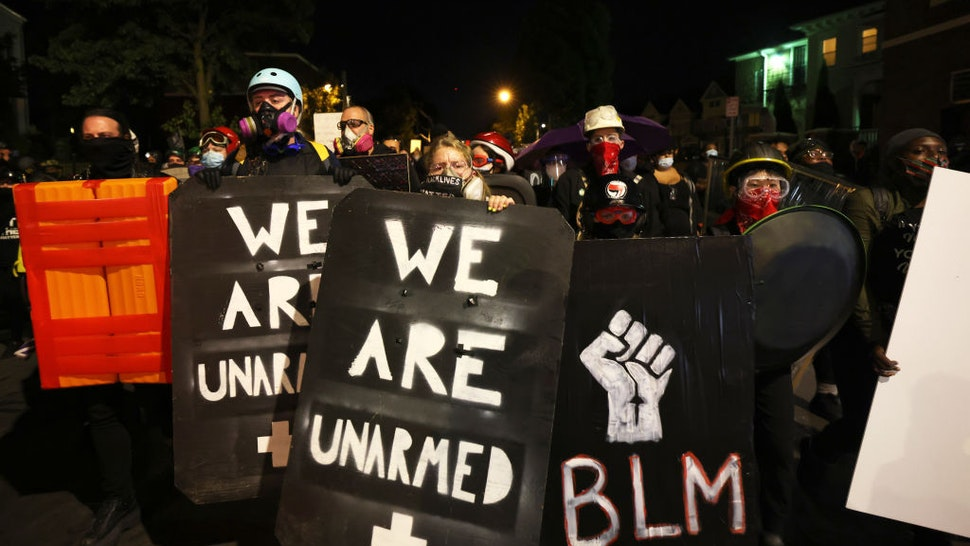 """ROCHESTER, NEW YORK - SEPTEMBER 06: Demonstrators hold up homemade shields as they march towards the Public Safety building for Daniel Prude on September 06, 2020 in Rochester, New York. Prude died after being arrested on March 23 by Rochester police officers who had placed a """"spit hood"""" over his head and pinned him to the ground while restraining him. This is the fifth consecutive night of protesting since the family released bodycam footage of Mr. Prude's arrest. (Photo by Michael M. Santiago/Getty Images)"""