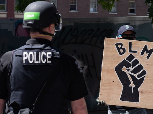 SEATTLE, WASHINGTON - AUGUST 9: A police officer stands in front of a Black Lives Matter sign during the Seattle Police Officers Guild√¢s rally to stop defunding of the Seattle Police Department on Sunday, August 9, 2020 at Seattle City Hall. The Seattle City Council passed a resolution to reduce the Seattle Police Department by up to 100 officers through layoffs but the council failed to pass a 50% cut of the Police Department√¢s remaining 2020 budget on August 5, 2020. (Photo by Noah Riffe/Anadolu Agency via Getty Images)