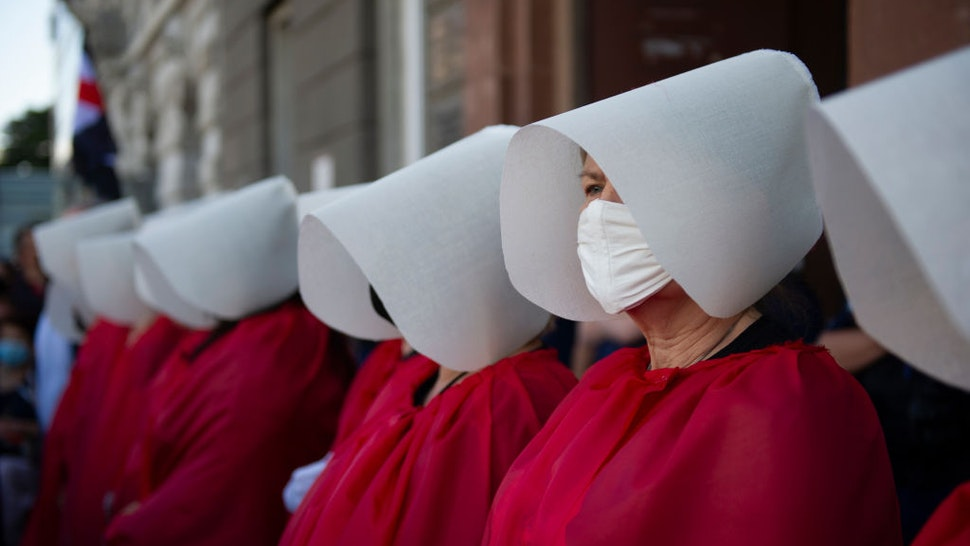 Demonstrators wearing protective face masks are dressed as the Handmaids from the dystopian novel The Handmaid's Tale from the Canadian author Margaret Atwood perform during an anti-domestic violence protest on July 24, 2020 in Warsaw, Poland. Thousands of demonstrators took part in a protest against government plan to pull out of an international treaty on preventing and combating domestic violence. (Photo by Aleksander Kalka/NurPhoto via Getty Images)