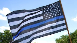 """A demonstrator holds a """"Thin Blue Line"""" flag and a sign in support of police during a protest outside the Governors Mansion on June 27, 2020 in St Paul, Minnesota. A group called """"Bikers for 45"""" advocating a pro-police stance arranged the protest and were met with counter-protesters calling for measures to defund police."""