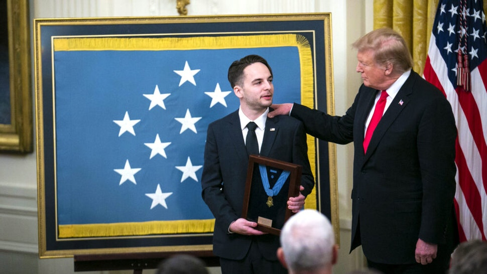 U.S. President Donald Trump, right, presents the Medal of Honor to Trevor Oliver, son of Staff Sergeant Travis Atkins, left, during a ceremony in the East Room of the White House in Washington, D.C., U.S., on Wednesday, March 27, 2019. Trump awarded the Medal of Honor posthumously to Staff Sergeant Travis Atkins, the first he bestowed to an Iraq War veteran.