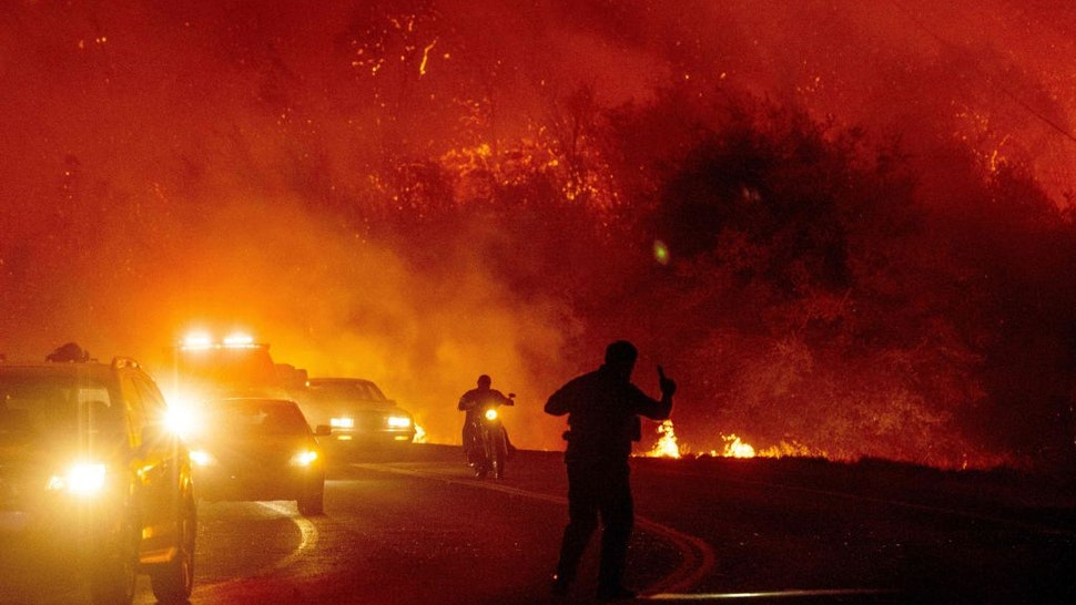 A law enforcement officer guides evacuees down a road surrounded by fire at the Bear fire in Oroville, California on September 9, 2020. - Dangerous dry winds whipped up California's record-breaking wildfires and ignited new blazes, as hundreds were evacuated by helicopter and tens of thousands were plunged into darkness by power outages across the western United States.