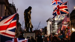 The statue of Britain's wartime leader Winston Churchill stands surrounded by Union Jack flags in London, England, on January 31, 2020. Britain's exit from the European Union, today at 11pm UK time (midnight in Brussels), comes more than three and a half years since the country's deeply polarising EU membership referendum, yet the moment brings to an end only the first stage of the Brexit saga, with the UK's future relationship with the bloc still to be negotiated. British Prime Minister Boris Johnson has insisted that the 11-month transition period, wherein arrangements continue practically unchanged, will not be extended past its December 31 expiration date and that a trade deal can be reached in that time. Critics argue that any such deal will have to be severely constrained in ambition to be negotiated in such a short period, and that workers' rights and other protections may be lost in the process. (Photo by David Cliff/NurPhoto via Getty Images)