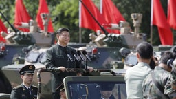 Xi Jinping, China's president, rides in a vehicle as he reviews People's Liberation Army (PLA) troops at the Shek Kong Barracks in Hong Kong, China, on Friday, June 30, 2017. Xi sought to reassure a divided Hong Kong of China's continued support for the former British colony, as pro-democracy protesters struggled to be heard behind road blocks and police lines. Photographer: Anthony Kwan/Bloomberg