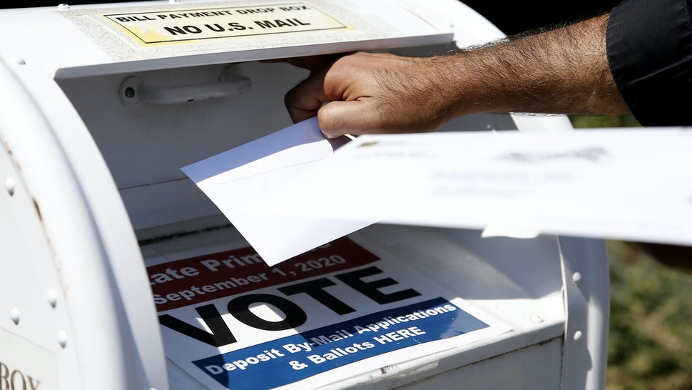 NEWTON - AUGUST 23: A voter drops a ballot into the box for mail-in ballots outside of Newton City Hall in Newton, MA on Aug. 23, 2020, where there's a crowded field in the primary race for the fourth Congressional Democratic nomination.