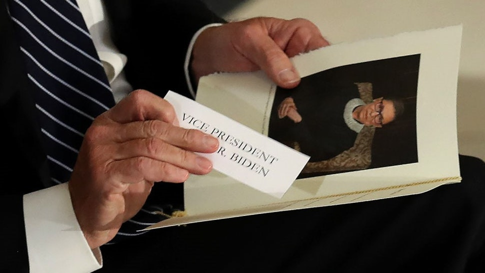 Former Vice President and Democratic presidential nominee Joe Biden puts his name tag into his program during a memorial for the late Associate Justice Ruth Bader Ginsburg in the Statuary Hall, where she lies in state at the US Capitol, September 25, 2020 in Washington, DC. (Photo by Chip Somodevilla / POOL / AFP) (Photo by