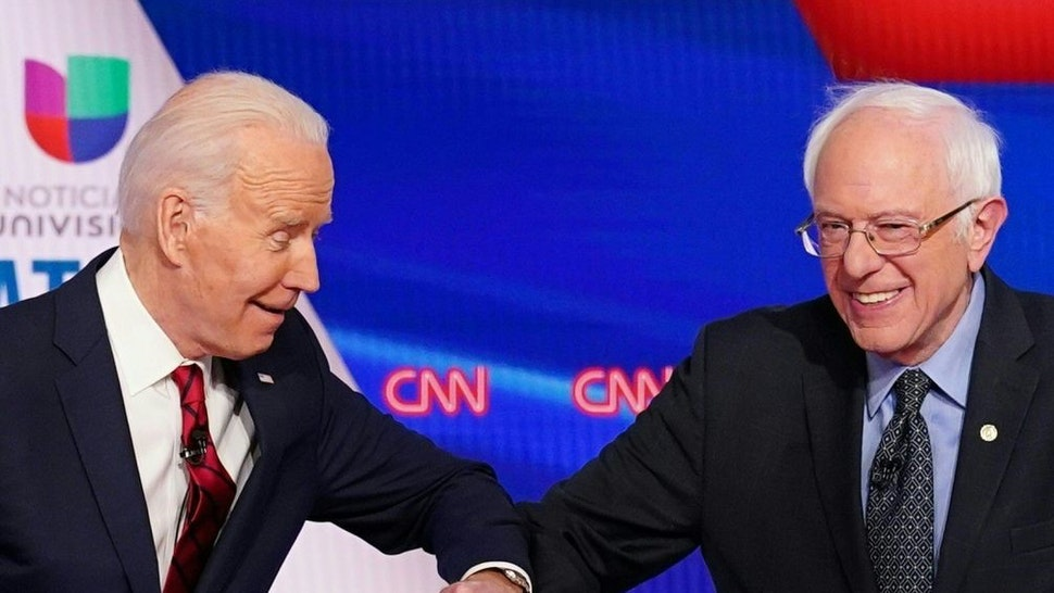 TOPSHOT - Democratic presidential hopefuls former US vice president Joe Biden (L) and Senator Bernie Sanders greet each other with a safe elbow bump before the start of the 11th Democratic Party 2020 presidential debate in a CNN Washington Bureau studio in Washington, DC on March 15, 2020. (Photo by Mandel NGAN / AFP) (Photo by