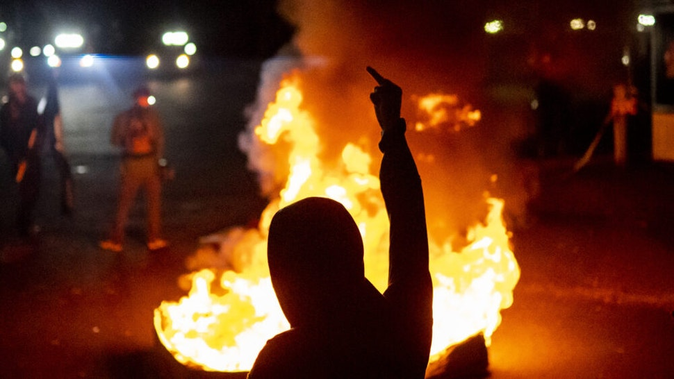 PORTLAND OR - SEPTEMBER 6: Protesters chant in front of a fire near the North police precinct during a protest against racial injustice and police brutality on September 6, 2020 in Portland, Oregon. Sunday marked the 101st consecutive night of protests in Portland.
