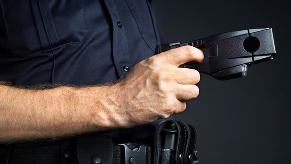 Police officer holding stun gun