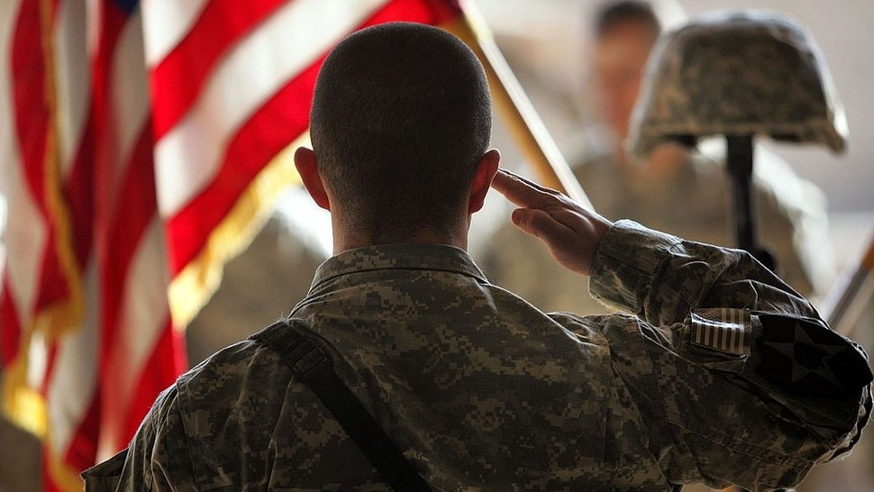RAMADI, IRAQ - JANUARY 15: A fellow soldier honors slain U.S. Army PFC Ming Sun, age 20 and a naturalized American citizen, at a memorial ceremony January 15, 2007 in Ramadi in Iraq's Anbar province. Sun was shot and killed by an insurgent sniper on January 9, 2007 while on combat operations with his unit from A Company 1st Battalion, 9th Infantry Regiment in Sufia, east of Ramadi. Sun was born in China and became an American citizen after moving to the United States with his family in 1996. U.S. forces and insurgents battle daily in the Ramadi area, which has some of the highest American casualty rates of the war. (Photo by