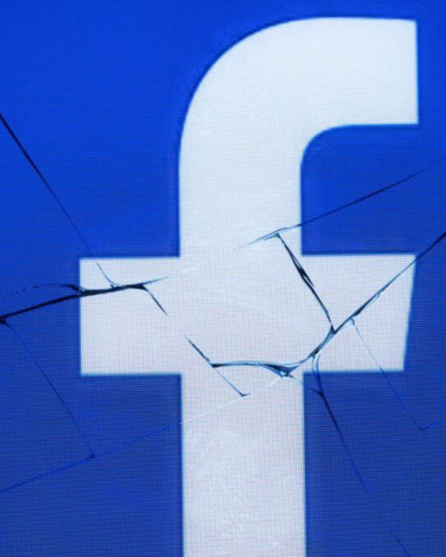 A picture taken in Paris on May 16, 2018 shows the logo of the social network Facebook on a broken screen of a mobile phone.