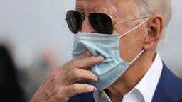 Wearing a face mask to reduce the risk posed by the coronavirus, Democratic presidential nominee Joe Biden speaks briefly with reporters before boarding a flight to Florida at New Castle County Airport October 13, 2020 in New Castle, Delaware.