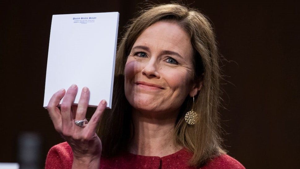 WASHINGTON, DC - OCTOBER 13: Supreme Court justice nominee Amy Coney Barrett holds up her notepad at the request of Sen. John Cornyn, R-Texas, on the second day of her Senate Judiciary Committee confirmation hearing in Hart Senate Office Building on October 13, 2020 in Washington, DC. Barrett was nominated by President Donald Trump to fill the vacancy left by Justice Ruth Bader Ginsburg who passed away in September. (Photo by