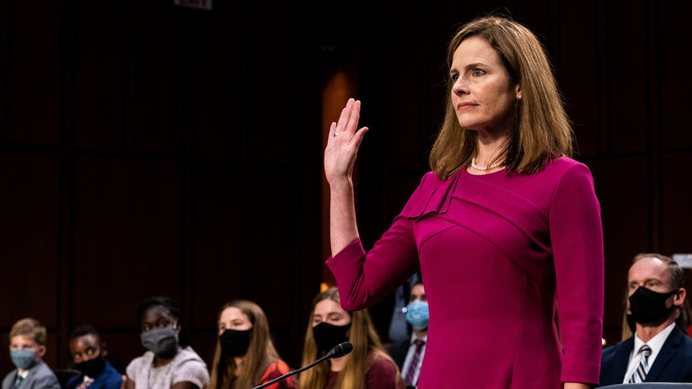 Supreme Court Justice nominee Judge Amy Coney Barrett stands as she is sworn in during the Senate Judiciary Committee confirmation hearing for Supreme Court Justice in the Hart Senate Office Building on October 12, 2020 in Washington, DC. With less than a month until the presidential election, President Donald Trump tapped Amy Coney Barrett to be his third Supreme Court nominee in just four years. If confirmed, Barrett would replace the late Associate Justice Ruth Bader Ginsburg. (Erin Schaff-Pool/Getty Images)
