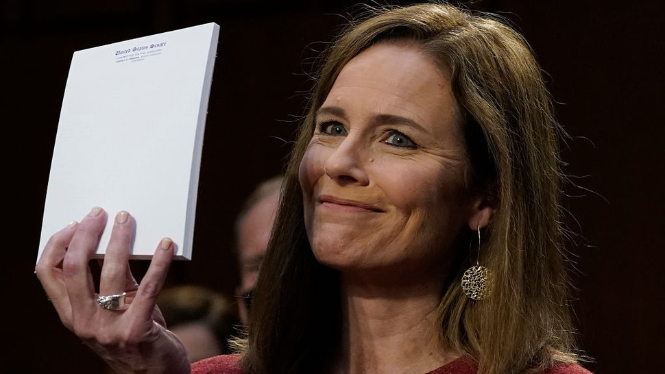 Judge Amy Coney Barrett, holds up a blank notepad after Senator John Cornyn asked her what documents she had on her desk during the second day of her Senate confirmation hearing to the Supreme Court on Capitol Hill in Washington, DC on October 13, 2020. - President Donald Trump's US Supreme Court nominee Amy Coney Barrett faces a sharply divided Senate October 13, 2020 for her first question-and-answer session, with Republicans praising her faith and qualifications and Democrats set to bombard her over healthcare. (Photo by Drew Angerer / POOL / AFP)