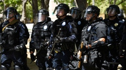 AURORA, CO - JUNE 27: Aurora police in full riot gear at the ready behind a police fence during a Elijah McClain protest in front of the Aurora Police department's headquarters at the Aurora Municipal Center June 27, 2020. Elijah McClain died August 30, 2019 several days after a struggle with Aurora police. Elijah became unconscious during the encounter with police August 24, 2019 and had a heart attack while being transported to a hospital. McClain died after being taken off life support. (Photo by Andy Cross/The Denver Post)