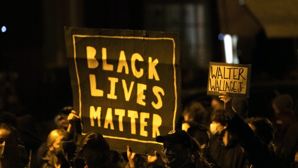 """PHILADELPHIA, PA - OCTOBER 27: Demonstrators holding placards reading """"BLACK LIVES MATTER"""" and """"WALTER WALLACE JR."""" during a protest near the location where Walter Wallace, Jr. was killed by two police officers on October 27, 2020 in Philadelphia, Pennsylvania. Protests erupted after the fatal shooting of 27-year-old Wallace Jr, who Philadelphia police officers claimed was armed with a knife."""
