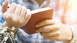 Human hand placed on the Bible, pray to God.