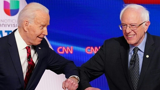 TOPSHOT - Democratic presidential hopefuls former US vice president Joe Biden (L) and Senator Bernie Sanders greet each other with a safe elbow bump before the start of the 11th Democratic Party 2020 presidential debate in a CNN Washington Bureau studio in Washington, DC on March 15, 2020.