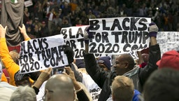 """Attendees hold """"Blacks For Trump"""" during a campaign rally with U.S. President Donald Trump in Pensacola, Florida, U.S., on Friday, Dec. 8, 2017. Trumpgave his most full-throated endorsement yet of Alabama Senate candidateRoy Moore, casting aside calls for to shun the former judge whos been accused of sexual misconduct while seizing on reports that questioned the credibility of his accuser."""