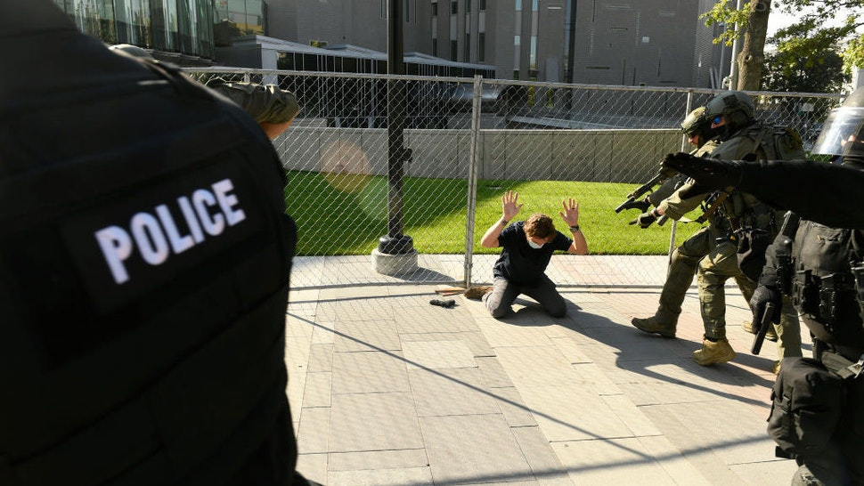 DENVER, COLORADO - OCTOBER 10: Police order a man to the ground after a shooting in Downtown Denver on October 10, 2020 in Denver, Colorado. The shooting happened as opposing rallies by far-right and far-left activists were ending. The shooter has been identified as Matthew Dolloff, center. He is being held for investigation of First Degree Murder in connection with this shooting. (Photo by Helen H. Richardson/MediaNews Group/The Denver Post via Getty Images)