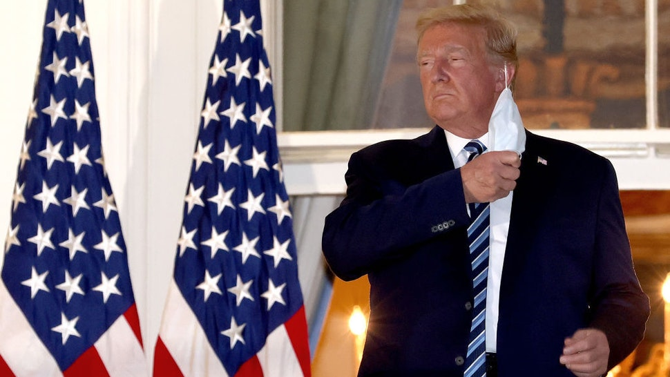 U.S. President Donald Trump removes his mask upon return to the White House from Walter Reed National Military Medical Center on October 05, 2020 in Washington, DC. Trump spent three days hospitalized for coronavirus. (Photo by Win McNamee/Getty Images)