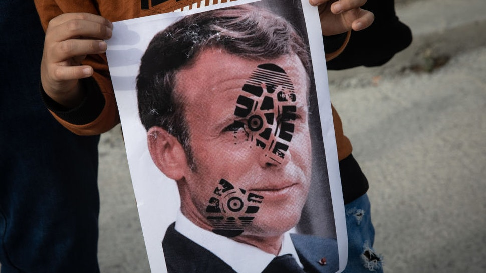 ISTANBUL, TURKEY - OCTOBER 25: A boy holds a poster showing the portrait of French President Emmanuel Macron during a protest against French president Emmanuel Macron on October 25, 2020 in Istanbul, Turkey. People gathered to protest against the recent statements by French President Emmanuel Macron regarding the beheading of a teacher that displayed cartoons of Prophet Muhammad in his class and the closure of some mosques in France. (Photo by Chris McGrath/Getty Images)