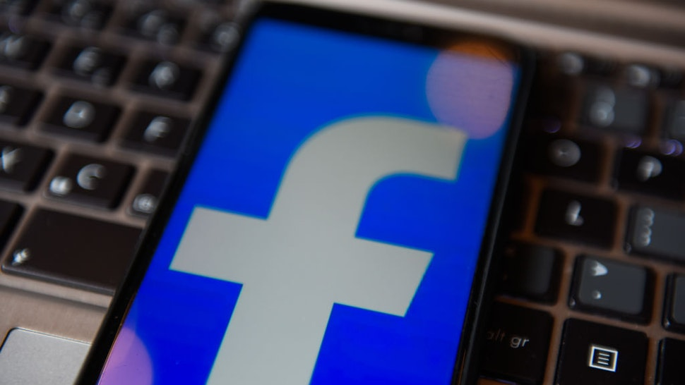 In this photo illustration a Facebook logo seen displayed on a smartphone with a laptop keyboard on the background.