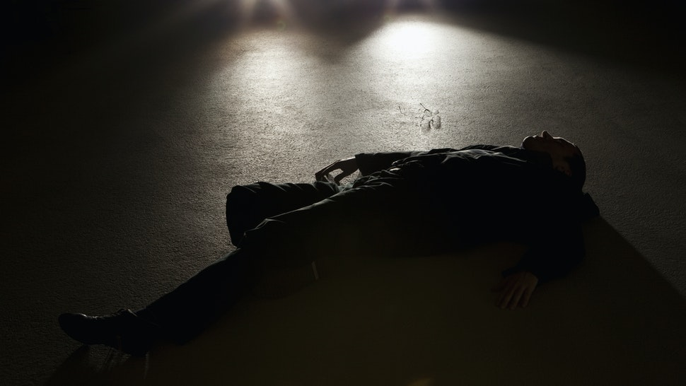 A man lying on the ground in front of a car at night - stock photo